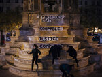 In this photo taken in the early hours of Monday Nov. 4, 2019, from left to right, Pauline, Clivia, France and Lea paste a slogan on a fountain reading