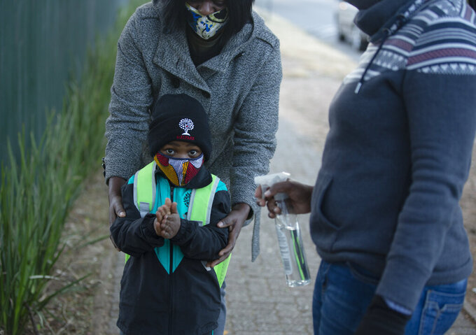A pupil has his hands sanitized on his return to school in Johannesburg, Monday July 6, 2020, as more of learners were permitted to return to class. Schools were shut down in March prior to a total country lockdown in a bid to prevent the spread of coronavirus and are now slowly being re-opened. (AP Photo/Denis Farrell)