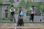 A man holds a child wearing a mask to curb the spread of the coronavirus as they watch a water fountain on Children's Day in Beijing on Monday, June 1, 2020. (AP Photo/Ng Han Guan)