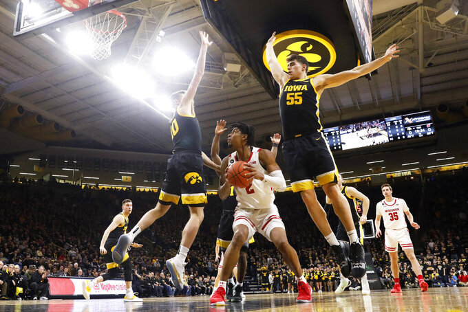 Wisconsin forward Aleem Ford, center, drives to the basket between Iowa's Joe Wieskamp, left, and Luka Garza, right, during the first half of an NCAA college basketball game, Monday, Jan. 27, 2020, in Iowa City, Iowa. (AP Photo/Charlie Neibergall)
