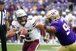 Montana quarterback Cam Humphrey (2) scrambles away from Washington's Sam Taimani in the first half of an NCAA college football game Saturday, Sept. 4, 2021, in Seattle. (AP Photo/Elaine Thompson)
