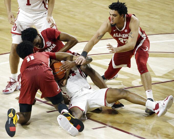 Alabama's Joshua Primo (11), Herbert Jones (1), and James Rojas (33) fight for the ball with Oklahoma's Elijah Harkless (24) during the second half of an NCAA college basketball game in Norman, Okla., Saturday, Jan. 30, 2021. (AP Photo/Garett Fisbeck)