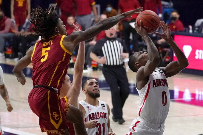 Southern California guard Isaiah White (5) blocks the shot of Arizona guard Bennedict Mathurin (0) during the second half of an NCAA college basketball game, Thursday, Jan. 7, 2021, in Tucson, Ariz. (AP Photo/Rick Scuteri)