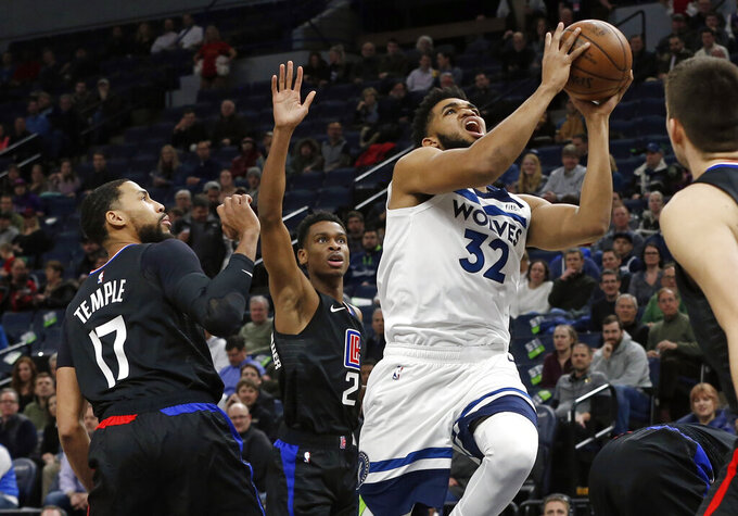 Minnesota Timberwolves' Karl-Anthony Towns, right, lays up as Los Angeles Clippers' Garrett Temple watches in the first half of an NBA basketball game Monday, Feb. 11, 2019, in Minneapolis. (AP Photo/Jim Mone)