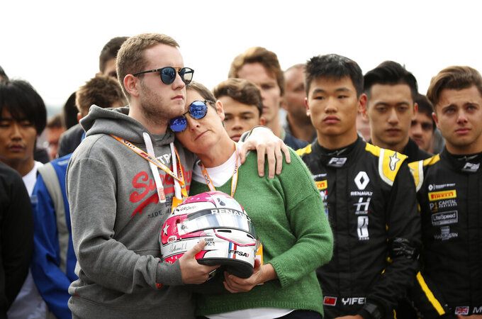 The mother and brother of Anthoine Hubert hold the helmet of Anthoine Hubert during a moment of silence at the Belgian Formula One Grand Prix circuit in Spa-Francorchamps, Belgium, Sunday, Sept. 1, 2019. The 22-year-old Hubert died following an estimated 160 mph (257 kph) collision on Lap 2 at the high-speed Spa-Francorchamps track, which earlier Saturday saw qualifying for Sunday's Formula One race. (AP Photo/Francisco Seco)