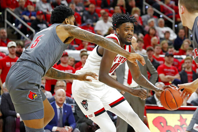 FILE - In this Feb. 1, 2020, file photo, North Carolina State's D.J. Funderburk (0) drives the ball as Louisville's Malik Williams (5) defends during the first half of an NCAA college basketball game in Raleigh, N.C. Funderburk is the Wolfpack's top returning scorer at 12.8 points for this season. (AP Photo/Karl B DeBlaker, File)