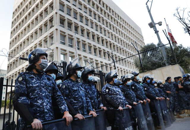 Lebanese riot police wear masks to help curb the spread of the coronavirus, as they stand guard in front the central bank building, where the anti-government protesters protest against the Lebanese central bank's governor Riad Salameh and against the deepening financial crisis, in Beirut, Lebanon, Thursday, April 23, 2020.   (AP Photo/Hussein Malla)
