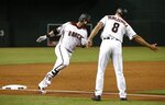 Arizona Diamondbacks' Daniel Descalso, left, gets ready to slap hands with third base coach Tony Perezchica (8) after Descalso's two-run home run against the Milwaukee Brewers in the first inning of a baseball game Wednesday, May 16, 2018, in Phoenix. (AP Photo/Ross D. Franklin)