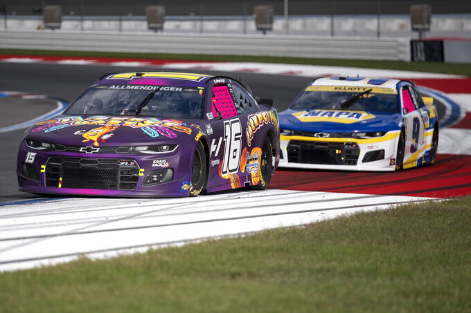 AJ Allmendinger (16) and Chase Elliott (9) compete during a NASCAR Cup Series auto racing race at Charlotte Motor Speedway, Monday, Oct. 11, 2021, in Concord, N.C. (AP Photo/Matt Kelley)
