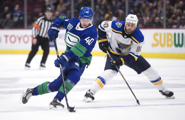 FILE - In this Nov., 5, 2019, file photo, Vancouver Canucks' Elias Pettersson (40), of Sweden, skates with the puck while being watched by St. Louis Blues' Ryan O'Reilly (90) during the second period of an NHL hockey game in Vancouver, British Columbia. If there's a polar opposite to the St. Louis Blues in terms of makeup and style, they'll face it in the Vancouver Canucks. The defending Stanley Cup champion Blues are big, heavy and not afraid to bruise their way through the playoffs. Vancouver relies more on speed and skill and has a fraction of the postseason experience. The first-round series between the teams will be decided by which team can dictate its preferred method of play. The Canucks hope to get star forward Elias Pettersson going and he's embracing the challenge of matching up against St. Louis center Ryan O'Reilly.(Darryl Dyck/The Canadian Press via AP, File)