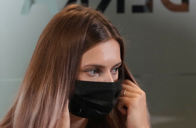 Belarusian Olympic sprinter Krystsina Tsimanouskaya, who came to Poland fearing reprisals at home after criticizing her coaches at the Tokyo Games, holds her face mask before she talks to journalists in Warsaw, Poland, Thursday, Aug. 5, 2021. (AP Photo/Czarek Sokolowski)