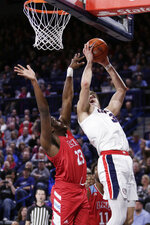 Gonzaga forward Filip Petrusev, right, shoots and is fouled by Loyola Marymount forward Jordan Bell during the first half of an NCAA college basketball game in Spokane, Wash., Thursday, Feb. 6, 2020. (AP Photo/Young Kwak)