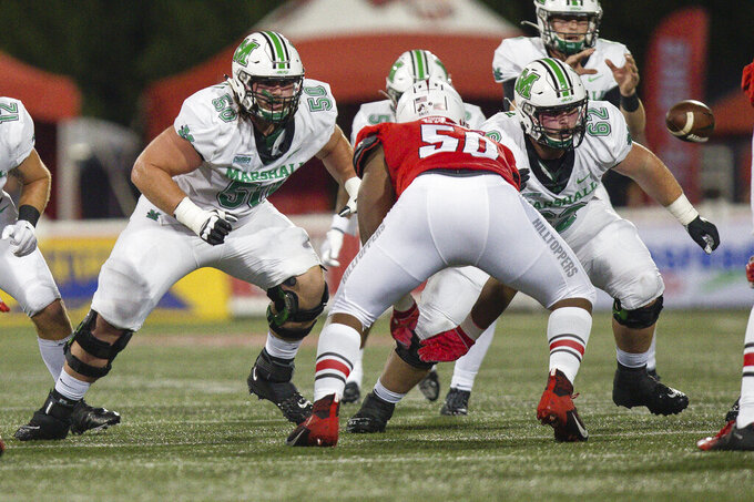 Marshall offensive linemen Will Ulmer (50) and Cain Madden (62) speed off the line of scrimmage after the snap during an NCAA college football game against Western Kentucky on Saturday, Oct. 10, 2020, in Huntington, W.Va. (Sholten Singer/The Herald-Dispatch via AP)