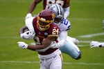 Washington Football Team running back Antonio Gibson (24) is tackled by Dallas Cowboys free safety Xavier Woods (25) in the first half of an NFL football game, Sunday, Oct. 25, 2020, in Landover, Md. (AP Photo/Susan Walsh)
