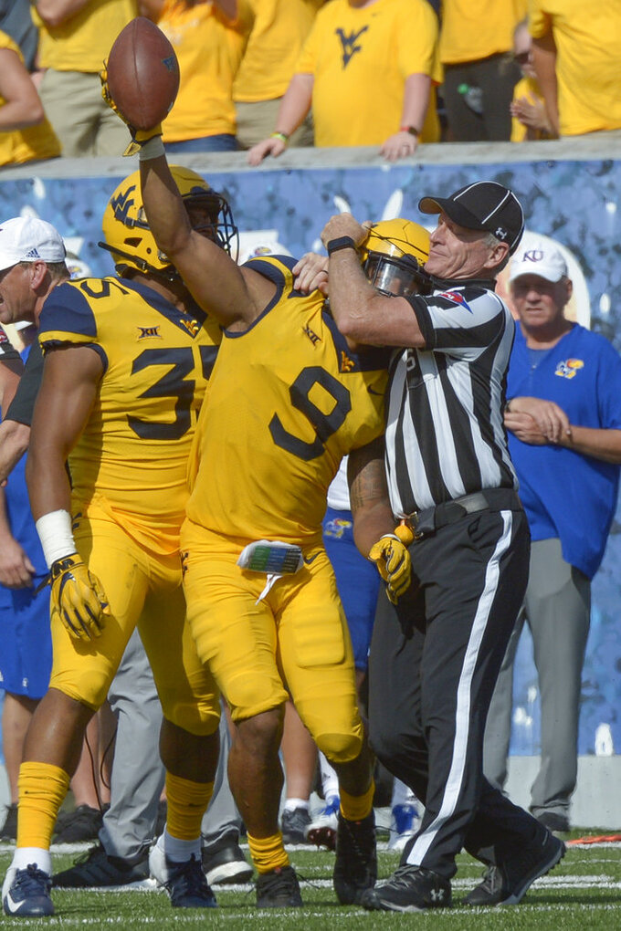 West Virginia safety Jovanni Stewart (9) is briefly caught in a referee's microphone wire after retrieving a fumble during the second half of an NCAA college football game against Kansas in Morgantown, W. Va., Saturday Oct. 6, 2018. (Craig Hudson/Charleston Gazette-Mail via AP)