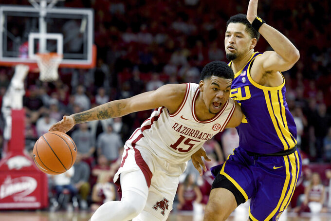 FILE - In this March 4, 2020, file photo, Arkansas guard Mason Jones(15) drives against LSU defender Skylar Mays (4) during the first half of an NCAA college basketball game in Fayetteville, Ark. Jones was selected to the Associated Press All-SEC first team announced Tuesday, March 10, 2020. Jones also tied for AP SEC Player of the Year. (AP Photo/Michael Woods, File)