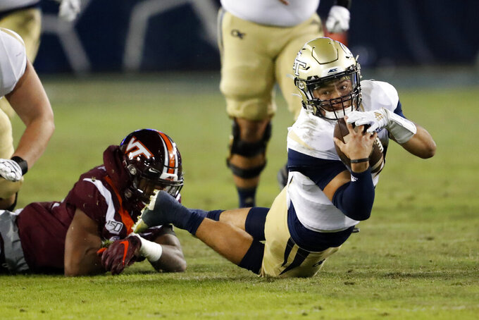 Georgia Tech quarterback Jordan Yates (13) dives for a first down after being hit by Virginia Tech linebacker Alan Tisdale (34) in the second half of an NCAA football game Saturday, Nov. 16, 2019, in Atlanta. (AP Photo/John Bazemore)
