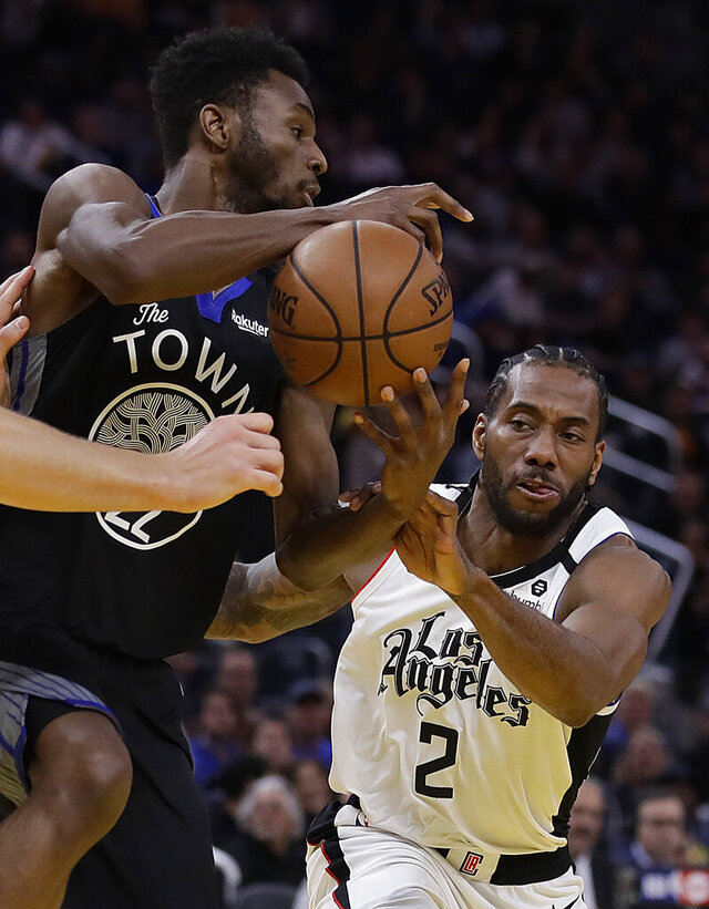 Golden State Warriors' Andrew Wiggins, left, keeps the ball from Los Angeles Clippers' Kawhi Leonard (2) in the second half of an NBA basketball game Tuesday, March 10, 2020, in San Francisco. (AP Photo/Ben Margot)