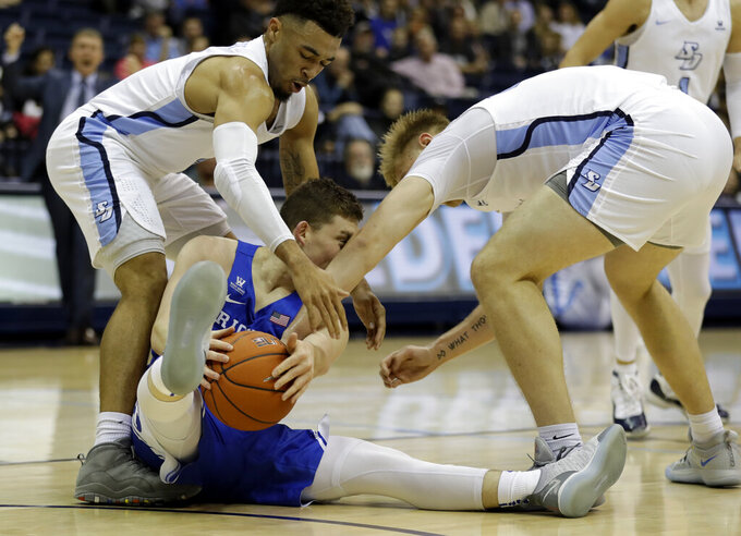 San Diego forward Yauhen Massalski, right, and teammate guard Olin Carter III, left, surround Brigham Young guard McKay Cannon, center, as he picks up a loose ball during the first half of an NCAA college basketball game Thursday, Feb. 14, 2019, in San Diego. (AP Photo/Gregory Bull)