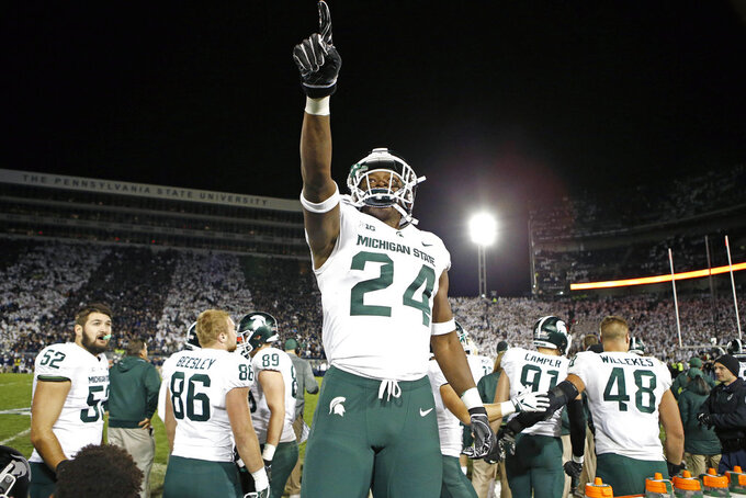 Michigan State's Elijah Collins (24) stands on the bench and celebrates after his team scored against Penn State with 19 seconds left in an NCAA college football game in State College, Pa., Saturday, Oct. 13, 2018. (AP Photo/Chris Knight)