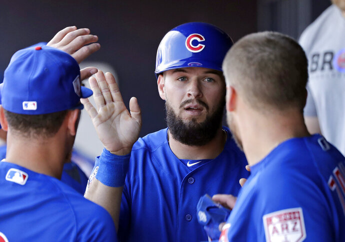 Chicago Cubs' David Bote is congratulated after scoring against the San Diego Padres in the fourth inning of a spring training baseball game Sunday, March 24, 2019, in Peoria, Ariz. (AP Photo/Elaine Thompson)