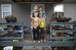 Tasha Lamm, 30, right, poses for a photo with her girlfriend, Alicia Mullins, 22, and Lamm's sons, Donovyn, 8, left, and Gabriel Bonice, 7, in front of their home in Bidwell, Ohio, on Monday, July 27, 2020.