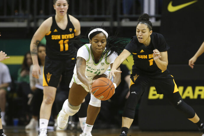 Oregon's Ruthy Hebard, center, battles Arizona State's Robbi Ryan, left, and Reili Richardson, right, for the ball during the first quarter of an NCAA college basketball game in Eugene, Ore., Sunday, Feb. 9, 2020. (AP Photo/Chris Pietsch)