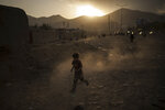 An Afghan boy plays on the side of a road as the sun sets in Kabul, Afghanistan, Wednesday, Sept. 22, 2021. (AP Photo/Felipe Dana)