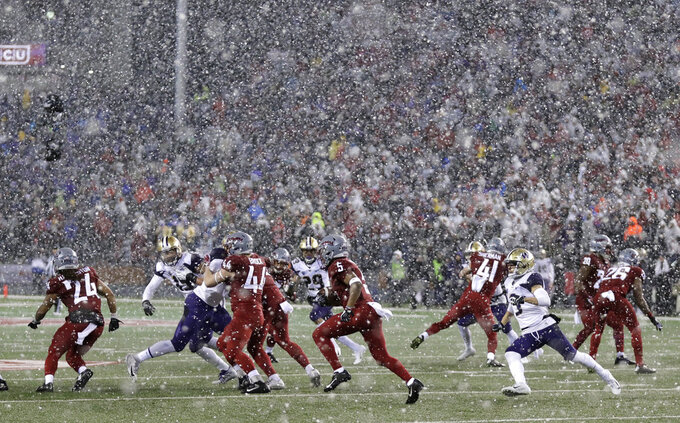 Washington State's Travell Harris, center, runs the ball against Washington as snow falls during the first half of an NCAA college football game, Friday, Nov. 23, 2018, in Pullman, Wash. (AP Photo/Ted S. Warren)
