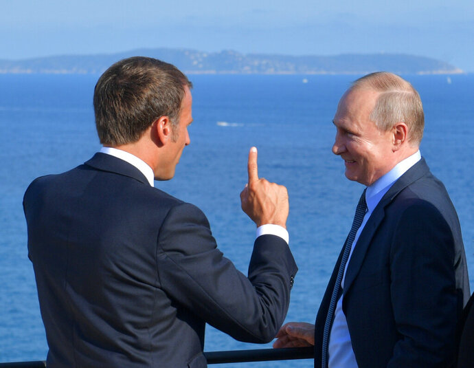 French President Emmanuel Macron, left, gestures as he talks with Russian President Vladimir Putin during their meeting at the fort of Bregancon in Bormes-les-Mimosas, southern France, Monday Aug. 19, 2019. French President Emmanuel Macron and Russian President Vladimir Putin are meeting to discuss the world's major crises, including Ukraine, Iran and Syria, and try to improve Moscow's relations with the European Union. (Alexei Druzhinin, Sputnik, Kremlin Pool Photo via AP)