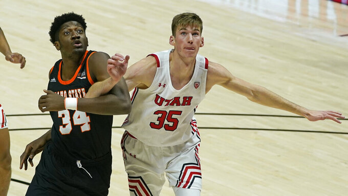 Utah center Branden Carlson (35) and Idaho State forward Gedeon Buzangu (34) battle for position under the boards during the first half of an NCAA college basketball game Tuesday, Dec. 8, 2020, in Salt Lake City. (AP Photo/Rick Bowmer)