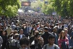 Opposition demonstrators throng in a tree lined avenue during a rally to protest the former president's shift into the prime minister's seat in Yerevan, Armenia, Tuesday, April 17, 2018. Thousands of opposition supporters have been rallying since last weekend to protest what they think is Sargsyan's attempt to stay in power indefinitely. (Narek Aleksanyan, PAN Photo via AP)