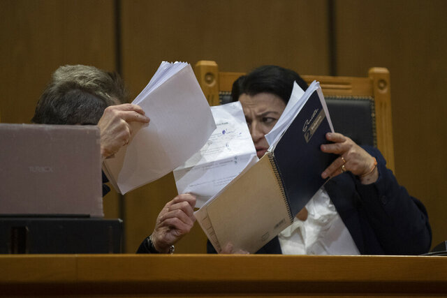 Presiding judge Maria Lepenioti consults a fellow judge as she reads the sentences during the Golden Dawn trial, in Athens, Thursday, Oct. 22, 2020. The court has sentenced the leadership of Greece's extreme-right Golden Dawn party to 13 years in prison, imposing the near-maximum penalty for running a criminal organization blamed for numerous violent hate crimes. The landmark ruling follows a five-year trial of dozens of top officials, members, and supporters of the organization founded as a Neo-Nazi group in the 1980s, that rose to become Greece's third-largest political party during a major financial crisis in the previous decade. (AP Photo/Petros Giannakouris)