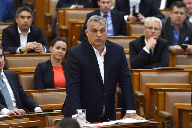 Hungarian Prime Minister Viktor Orban replies to an oppositional MP during a question and answer session of the Parliament in Budapest, Hungary, Budapest, Hungary, Monday, March 30, 2020. Hungary's parliament on Monday approved a bill giving Prime Minister Viktor Orban's government extraordinary powers during the coronavirus pandemic, without setting an end date for their expiration.  The bill was approved by Orban's Fidesz party and other government supporters by 137 votes in favor to 53 against. (Zoltan Mathe/MTI via AP)