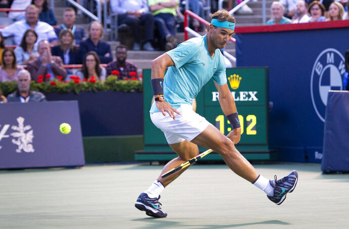Rafael Nadal, of Spain, hits the ball between his legs to return to Fabio Fognini, of Italy, during the Rogers Cup men's tennis tournament Friday, Aug. 9, 2019, in Montreal. (Paul Chiasson/The Canadian Press via AP)