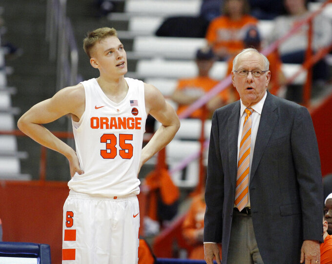 FILE - In this Oct. 31, 2018, file photo, Syracuse head coach Jim Boeheim, right, talks to his son Buddy Boeheim, left, during the first half of an NCAA college basketball game against Le Moyne in Syracuse, N.Y. With five freshmen on the roster this year and his dad counting more on him than most probably anticipated, he's delivered. Syracuse travels to Virginia Tech on Saturday, Jan. 18, 2020. (AP Photo/Nick Lisi, File)