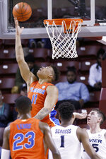 Florida's Keyontae Johnson goes up for a reverse layup over Xavier's defense in the first half of an NCAA college basketball game during the finals of the Charleston Classic Sunday, Nov. 24, 2019, in Charleston, SC. At far left is Xavier head coach Travis Steele. (AP Photo/Mic Smith)
