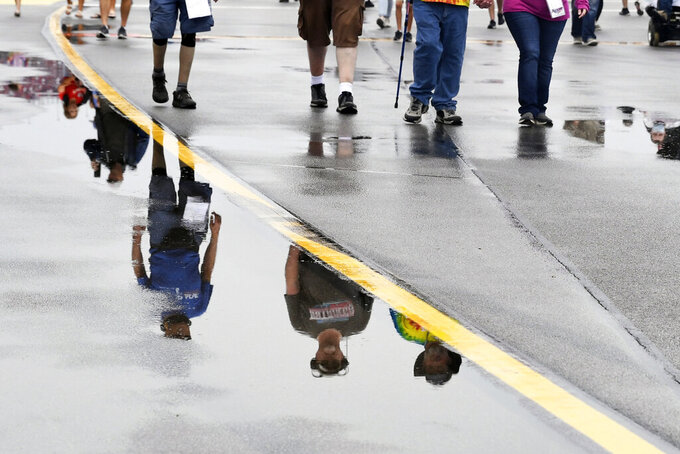 Fans walking in pit row are reflected in puddles of rainwater before a NASCAR Cup series auto race Sunday, Oct. 3, 2021, in Talladega, Ala. (AP Photo/John Amis)
