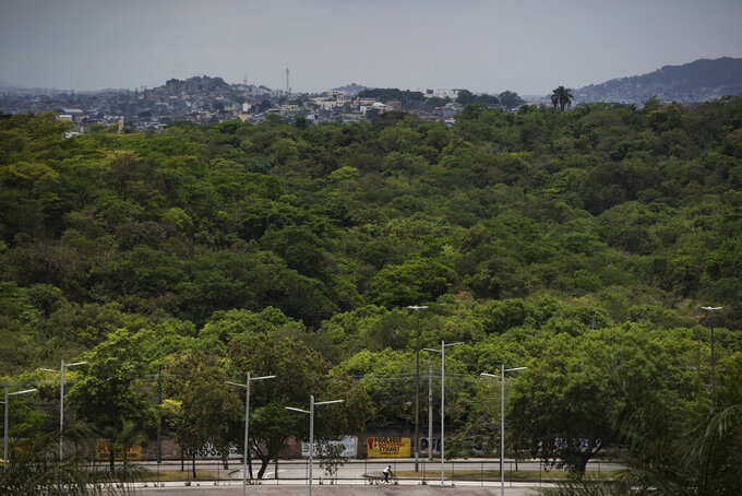 In this Nov. 7, 2019 photo, a man rides his bicycle past land that is part of a planned F1 racetrack in Rio de Janeiro, Brazil. The Company Rio Motorpark says it will pay up to $170 million to construct a track in the seaside city's impoverished Deodoro region. (AP Photo/Leo Correa)