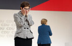 Newly elected CDU chairwoman Annegret Kramp-Karrenbauer, left, reacts during the party convention of the Christian Democratic Party CDU in Hamburg, Germany, Friday, Dec. 7, 2018, after German Chancellor Angela Merkel, right, didn't run again for party chairmanship after more than 18 years at the helm of the party. (AP Photo/Michael Sohn)