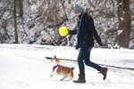 Ally Graziani of Pittsburgh, Pennsylvania and her dog Freya play fetch with a yellow balloon at Ritter Park after a winter storm on Monday, Feb. 15, 2021, in Huntington, W.Va. (Ryan Fischer/The Herald-Dispatch via AP)