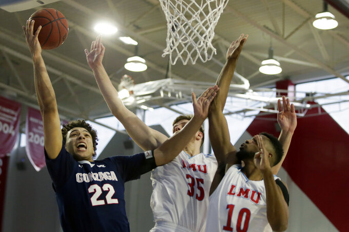 Gonzaga forward Anton Watson, left, drives past Loyola Marymount forward Ivan Alipiev, center, and forward Jonathan Dos Anjos, right, to shoot during the first half of an NCAA college basketball game in Los Angeles, Saturday, Jan. 11, 2020. (AP Photo/Alex Gallardo)
