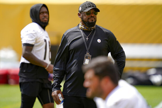 Pittsburgh Steelers head coach Mike Tomlin, center, watches the team as guard David DeCastro, bottom warms up and wide receiver JuJu Smith-Schuster, left , walks by during an NFL football training camp practice, Monday, Aug. 24, 2020, in Pittsburgh. (AP Photo/Keith Srakocic)