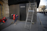 Workers set up steel protections on a shop windows on the Champs-Elysees, Friday, March 22, 2019. French President Emmanuel Macron has announced that soldiers will be deployed across the country to help maintain security during yellow vest protests planned this weekend. (AP Photo/Christophe Ena)