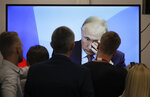 Journalists watch a broadcast of the meeting of Russian President Vladimir Putin and Japanese Prime Minister Shinzo Abe at the Eastern Economic Forum in Vladivostok, Russia, Monday, Sept. 10, 2018. (AP Photo/Dmitri Lovetsky)