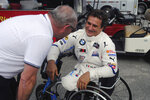 Alex Zanardi, right, speaks with an unidentified person in the garage at Daytona International Speedway in Daytona Beach, Fla., Friday, Jan. 4, 2018, where he is preparing for the Rolex 24, an endurance race at Daytona in late January. Zanardi is still racing 17 years after both his legs were severed in a crash. The Italian is now behind the wheel of a BMW that has been customized for Zanardi to race without his prosthetic legs. (AP Photo/Mark Long)