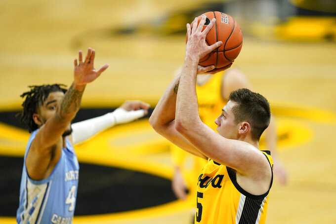 Iowa guard CJ Fredrick, right, shoots a 3-point basket ahead of North Carolina guard R.J. Davis, left, during the first half of an NCAA college basketball game, Tuesday, Dec. 8, 2020, in Iowa City, Iowa. (AP Photo/Charlie Neibergall)