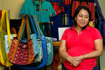 Maria Chavalan-Sut of Guatemala stands next to items she has made at the Wesley Memorial United Methodist Church in Charlottesville, Va., on Wednesday, July 17, 2019. She uses fabric that a son has mailed to her from Guatemala to make a range of goods. She can't sell them, but she accepts donations in exchange. (AP Photo/Jose Luis Magana)