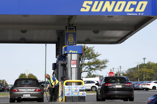 FILE- In this Sept. 21, 2017, a Sunoco employee fills gas onto a vehicle at the Cheesequake Rest Area in South Amboy, N.J. AAA Mid-Atlantic says the average price of a gallon of regular gas in New Jersey on Friday, July 23, 2020, was unchanged from the previous week at $2.19. Drivers were paying $2.80 a gallon at this time last year. (AP Photo/Julio Cortez, File)