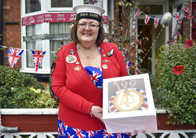 Kath Ryan delivers a cake to celebrate the 100th birthday of Leonora Jeffreys, a former Doodlebug spotter during World War II in Birmingham, England, Monday, Oct. 5, 2020. Ryan is behind Cakes 4 Casualties, baking thousands of cakes for service people who have been injured, many as they recover from wounds in hospital. (AP Photo/Rui Vieira)